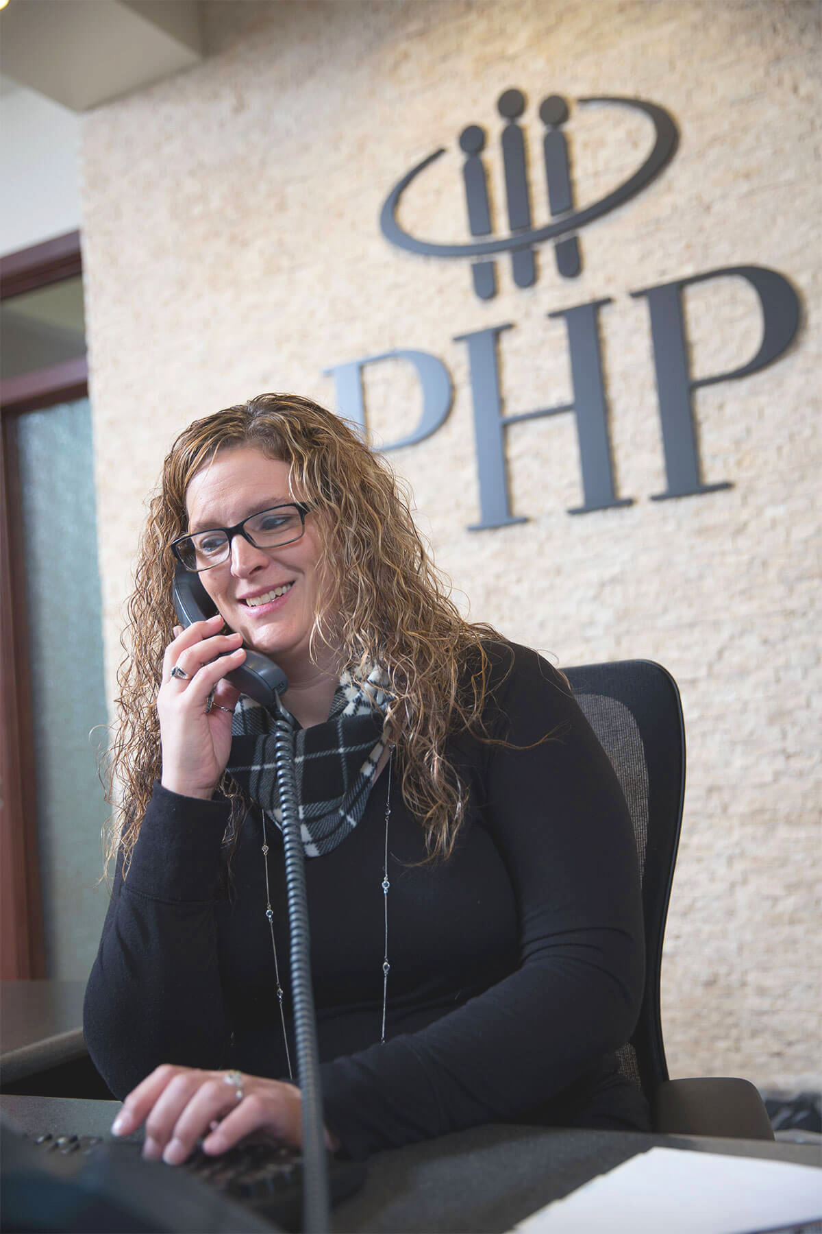 A receptionist at Physicians Health Plan is on the phone helping a customer.